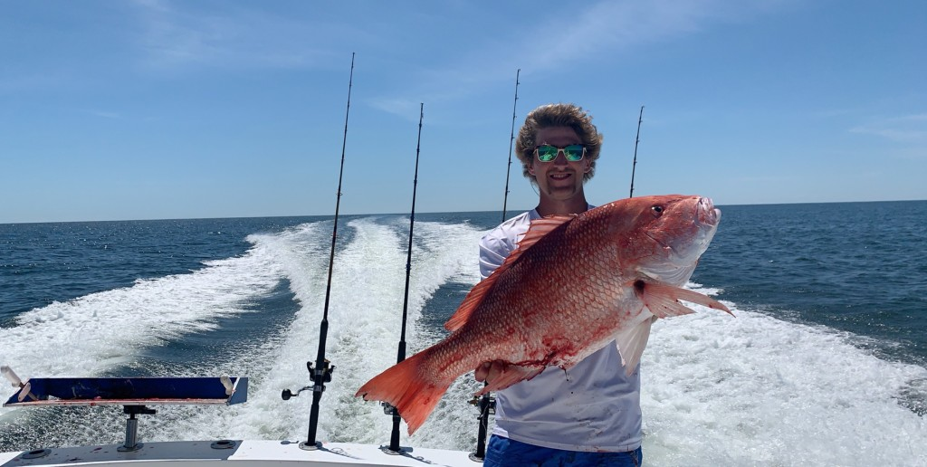 man holding up red snapper on back of boat in gulf