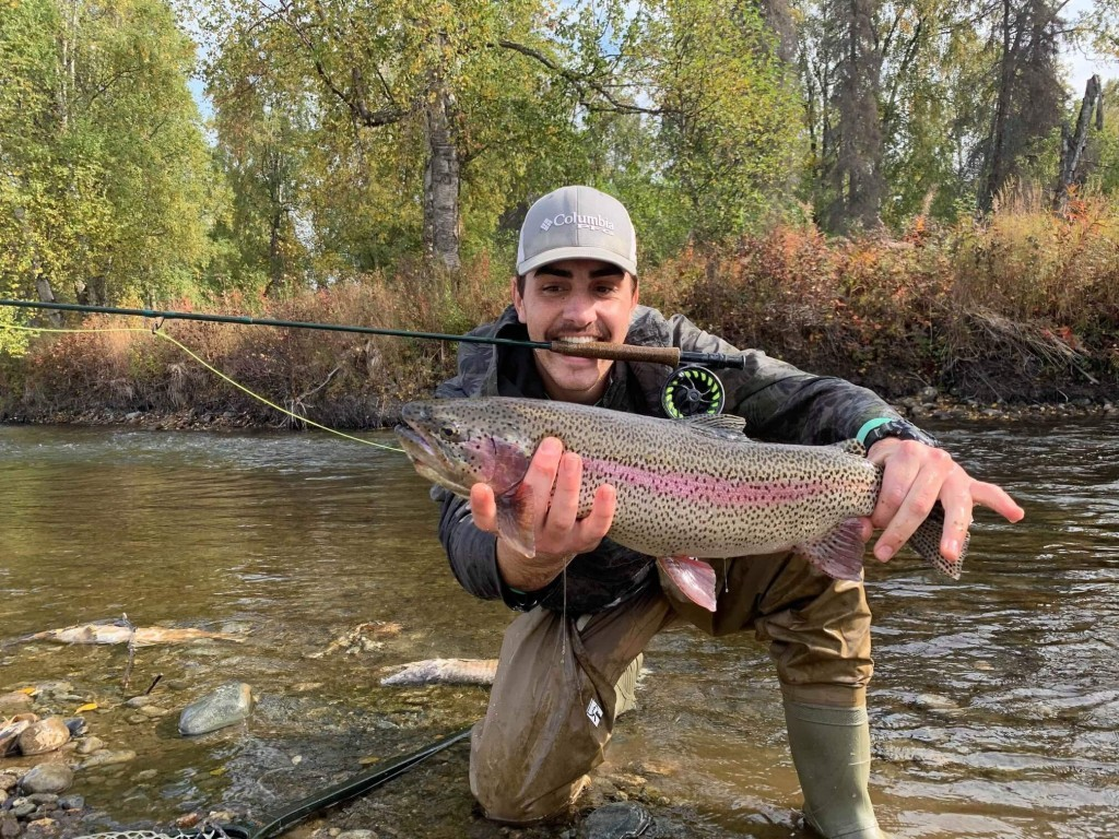 Man Holding Rainbow Trout on a River in Alaska